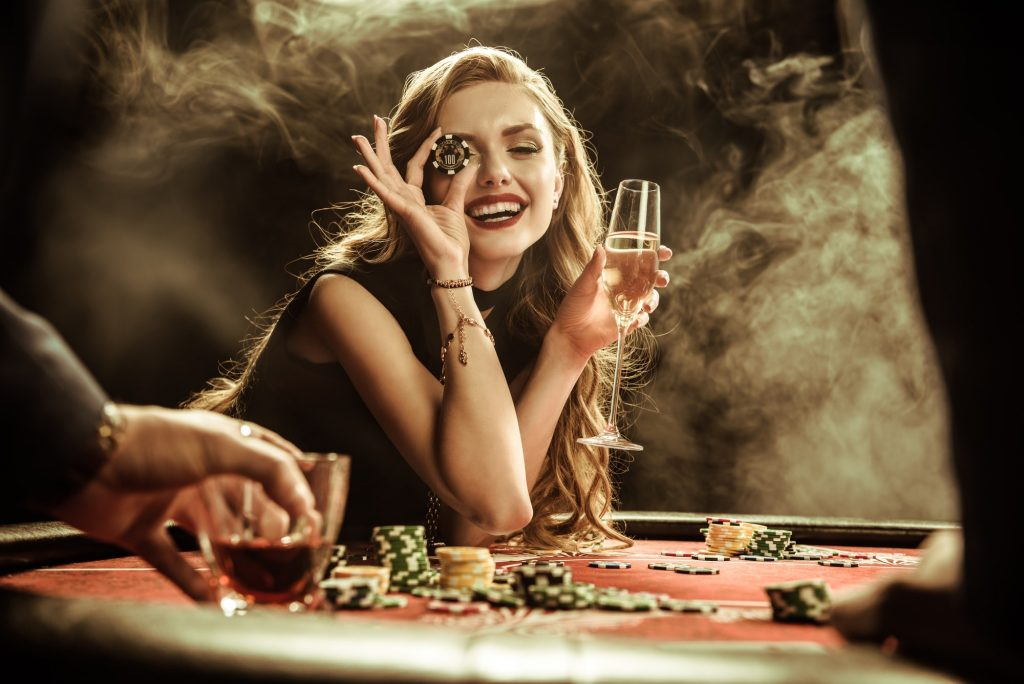 portrait of smiling woman with drink and poker chip playing poker